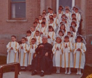 This is my first communion. I am in the first row with my two brothers. My older brother Joe on the left of me, my twin brother Paul on my right.