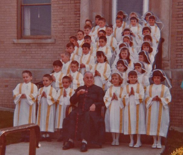 This is a picture taken from my first communion. The three boys on the left of the priest are myself and my brothers. My oldest brother, Joe, is on the left. I am in the middle, and my twin Paul, is to the right. This was taken at St Charles Parish in Dover, NH.